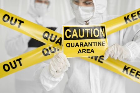 Epidemiologists a man and a woman in protective clothing are in a restricted area with a danger sign. Yellow line Keep Out Quarantine. Entrance is forbidden in quarantine zone. Coronavirus, covid-19.