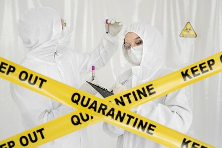 Epidemiologist woman in protective clothing is in a restricted area with a planchette. Infected blood sample in sample tube in hand of scientist doctor biohazard protection clothing