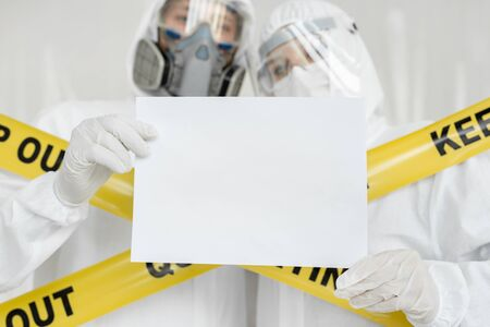 Doctors epidemiologists man and woman are holding white empty blank board with place for text image. Yellow line Keep Out Quarantine Standard-Bild
