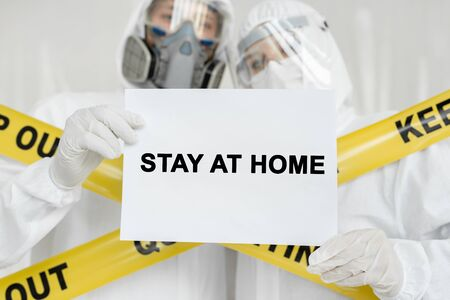 Doctors epidemiologists man and woman are holding poster with sign Stay At Home over white background. Yellow line Keep Out Quarantine