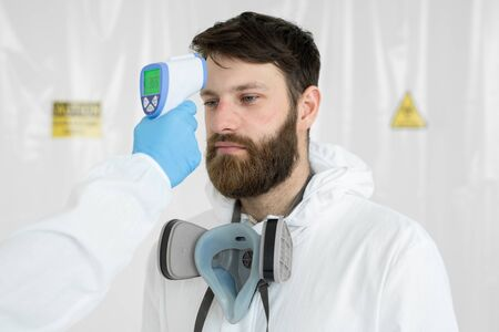 Doctor measures the temperature with an infrared thermometer to his colleague of infectious diseases. Portrait of a man doctor scientist in a lab coat. Concept of coronavirus