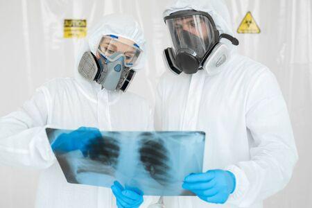 Epidemiologists in respirators examine the patients pneumonia on a radiograph Covid-19. Concept of coronavirus