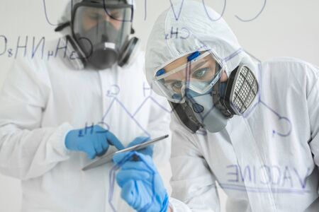 Woman scientist in laboratory writes chemical formula. Concept of Covid-19