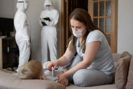 Mom measures babys temperature. Doctors in protective suits at sick patients at home. Coronavirus, covid-19