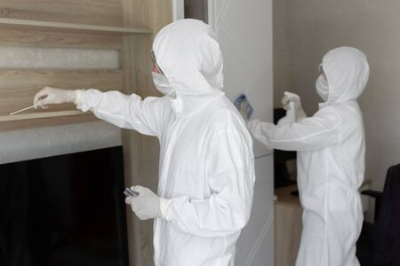 Virologists, people in protective suits carry out the disinfection in the apartment. Wipe furniture and take samples for contamination from the surface during a coronavirus epidemic. Covid - 19 Standard-Bild