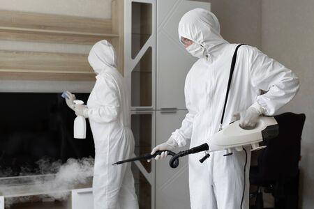 Coronavirus disinfection. People in hazmats making disinfection in flat, copy space, hot steam disinfection Standard-Bild
