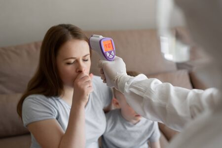 Doctor check patient body temperature using infrared forehead thermometer gun at home. Coronavirus, covid-19, high fever and cough
