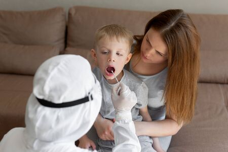 Doctor takes a cotton bud from child mouth to analyze the saliva, mucous membrane for DNA tests, COVID-19, to determine or presence of virus, SARS-CoV-2 epidemic, coronavirus concept