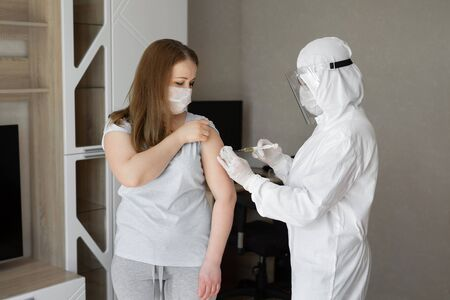 Doctor in personal protective suit or PPE inject vaccine shot to stimulating immunity of woman patient at risk of coronavirus infection. Coronavirus,covid-19 and vaccination concept Standard-Bild