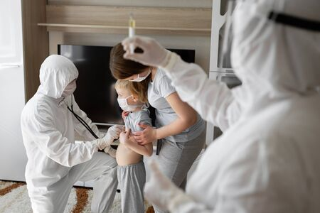 Pediatrician doctor examining sick child in face mask and a protective suit. Sick boy with his mother at home. Kids home treatment of virus. Coronavirus pandemic. Covid-19 outbreak