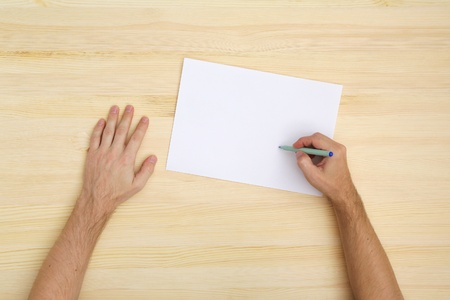 man writing on the paper, top view photo