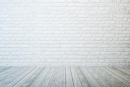 白いレンガの壁と木製の床と空の部屋