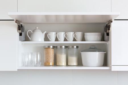 opened cupboard with kitchenware inside Standard-Bild