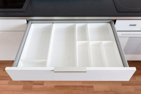 kitchen cabinets: opened white empty drawer Stock Photo