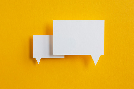 speak bubble: paper speech bubbles on yellow background Stock Photo