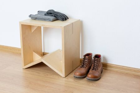White empty anteroom with wooden stool and leather boots Banque d'images