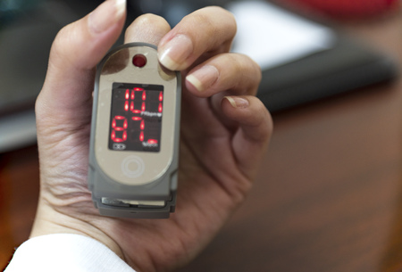 Pulse oximeter in a female patient's fingertip Фото со стока