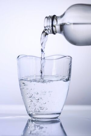 A glass of water pouring from a glass of bottle on a white background, close up, isolated.