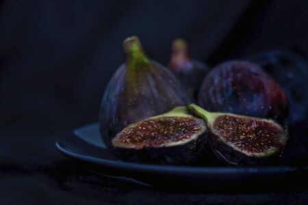 Exotic fig fruits in a blue plate, close up, isolated, still life photography