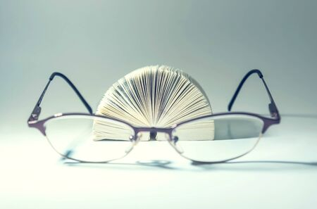 Eye glasses in front of a pocket book on a white table, close up, isolated