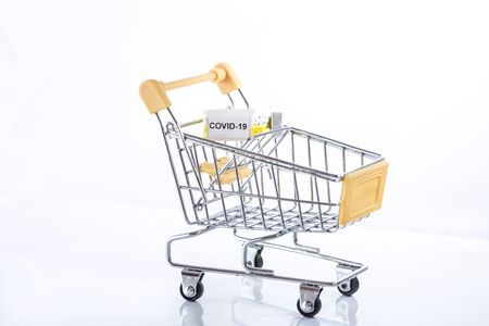 Yellow shopping cart with Covid-19 vaccine on a white background, isolated, close up. Be careful with coronavirus while shopping!