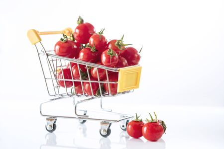 Cherry tomatoes in a metal shopping cart on a white background, close up, macro photography