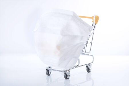 Shopping cart with white face mask on a white background, isolated, close up Stok Fotoğraf