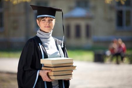Portret van jonge vrouwelijke afgestudeerde met stapel boeken, in het zonlicht, met wazig college gebouw op de achtergrond  Stockfoto