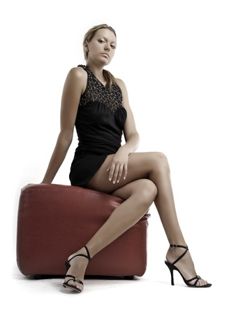 pouffe: Young blond woman in black dress and shoes on a high heels sitting on pouffe