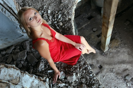 Young beautiful blond woman in a red dress sitting on the edge of the floor in abandoned construction photo