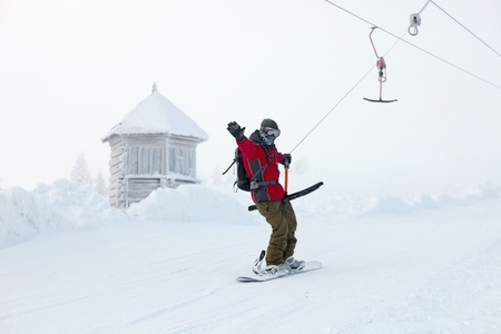 Snowboarder rises up the mountain on sky-lift Stock Photo - 16617975