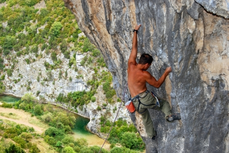 Rock climber battles his way up an arch in Rodellar Stock Photo - 16617982