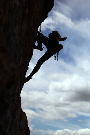 rockclimb: Silhouette of rock climber climbing a cliff with cloudy sky background