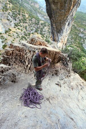 Rock climber winding a rope after ascent, top view on the climber with picturesque mountain background  Rodellar Canyon, Spain photo