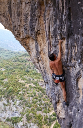 Rock climber battles his way up an arch in Rodellar Canyon, Spain  photo