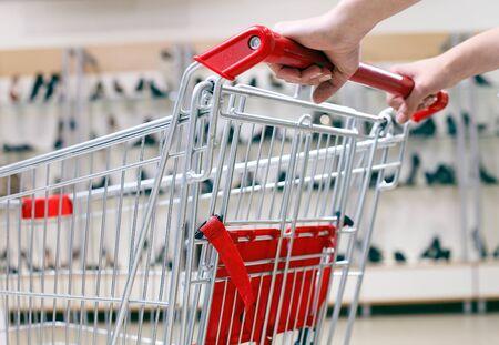 carro supermercado: Mujer empujando carro de la compra en la tienda de zapatos, primer plano Foto de archivo