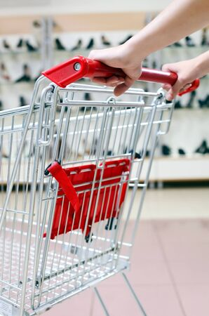 Woman pushing shopping cart in shoe store, close-up  photo