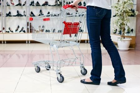 tienda de zapatos: Mitad inferior cintura para abajo la imagen de la mujer en los pantalones vaqueros que empujan un carrito de compras en una tienda de zapatos Foto de archivo