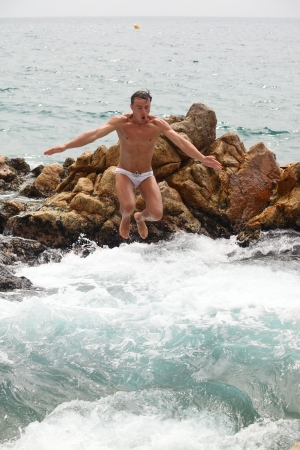 Young man jumping into water from the pile of rocks, vertical view  photo