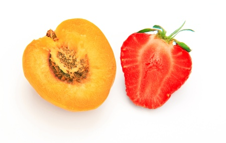 Apricot and strawberry cut open on white background  photo