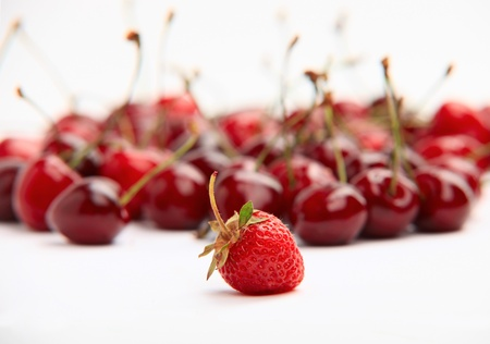 Single strawberry standing out on the background of the group of cherries  photo