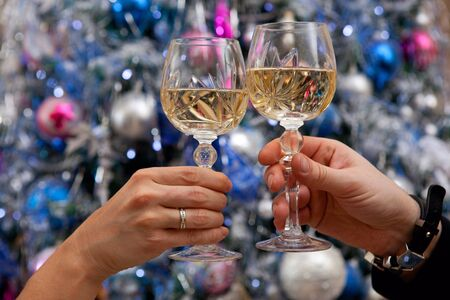 Hands holding glasses of champagne against new year tree photo