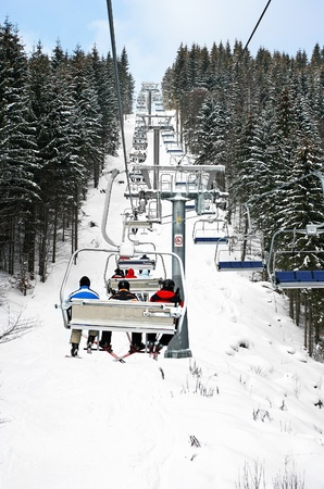skiers: Skiers in chairlift