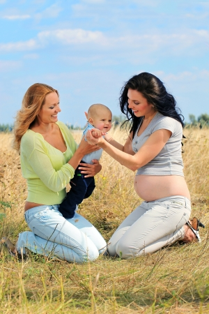 pregnant blonde: Beautiful blond woman with son and her pregnant girlfriend