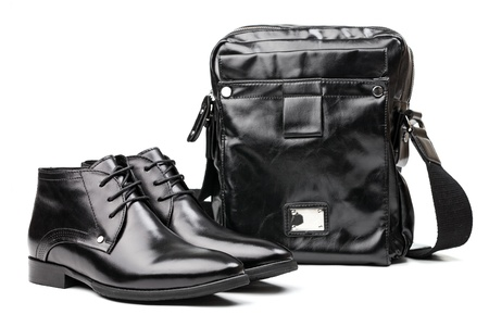 Pair of black men boots and messenger bag over white photo