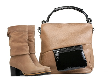 Pair of female boots and handbag over white photo