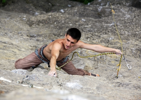 thrill: Rock climber preparing to the next move Stock Photo