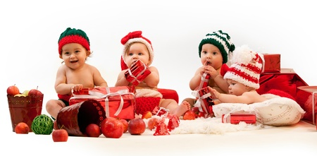 hispanic kids: Four babies in xmas costumes playing among gifts