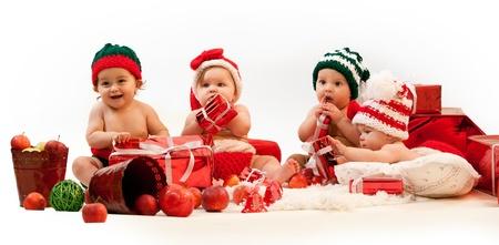 baby kerst: Vier baby's in xmas kostuums te spelen onder de geschenken