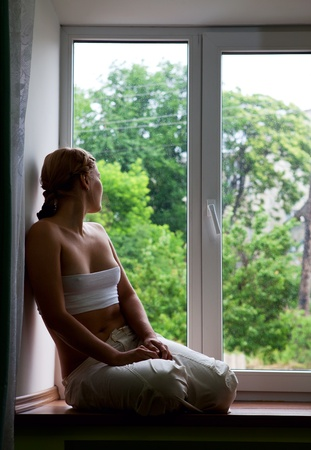 see through: Young woman sitting by a window